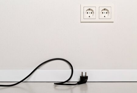 Black power cord cable unplugged with european wall outlet on white plaster wall  with copy space