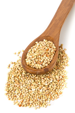 Raw, natural, uncooked buckwheat seed kernels in wooden spoon over white background