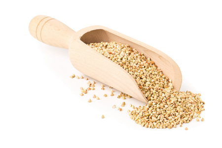 Raw, natural, uncooked buckwheat seed kernels in wooden scoop over white background