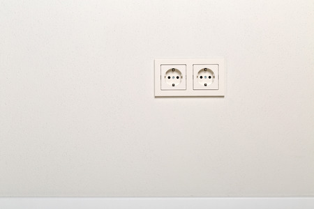 Empty, unplugged european wall outlet on white plaster wall with copy space Lizenzfreie Bilder
