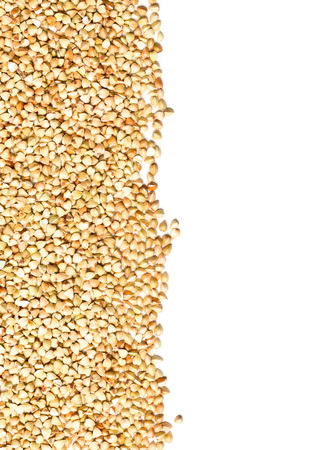 Raw, natural, uncooked buckwheat seed kernels border frame over white background