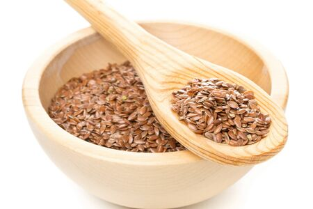 Raw, unprocessed linseed or flax seed in wooden bowl and wood spoon over white background