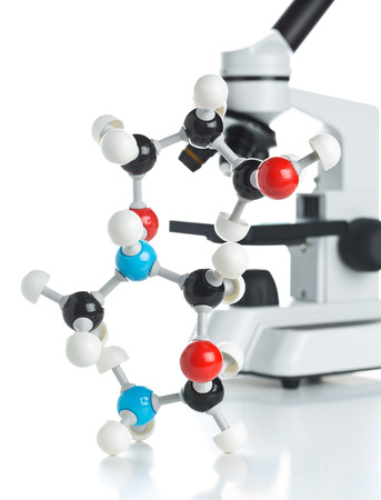 Microscope with molecule model over white background