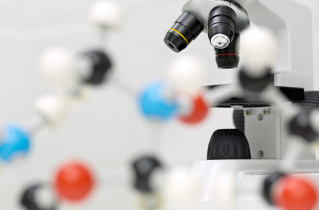 Microscope behind out of focus molecule model over white background