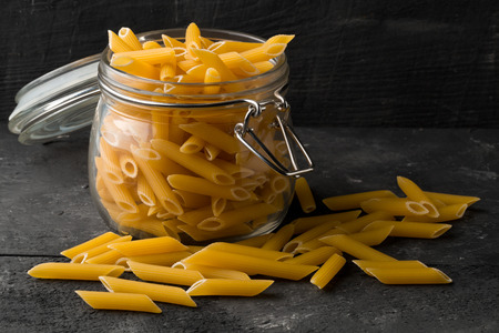 round: Raw, uncooked, dry penne pasta noodles in glass jar on black table background