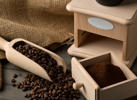 Coffee beans in wooden scoop and ground coffee in wooden scoop with coffee bean grinder on dark wooden table background
