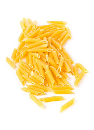 Heap of dried, raw, uncooked penne pasta over white background