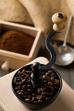 Coffee beans in coffee bean grinder with ground coffee powder on dark wooden table background