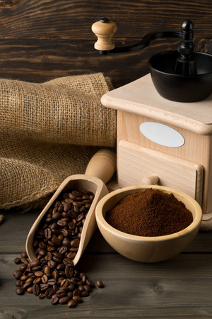 Coffee beans in wooden scoop and ground coffee in wooden bowl with coffee bean grinder on dark wooden table background