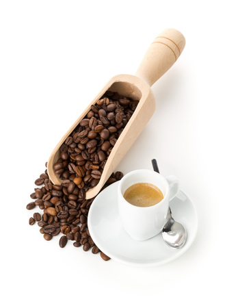 Coffee beans in wooden scoop and cup of espresso on white background