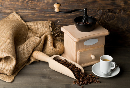 Coffee grinder with coffee beans in wooden scoop and cup of espresso on dark wooden table background