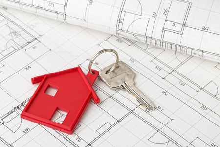 House door key with red house key chain pendant on building plans background