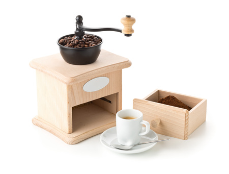 Coffee grinder with ground coffee, coffee beans and cup of espresso on white background