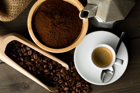 Coffee beans, ground coffee powder and cup of espresso with stovetop coffee maker on dark wooden table background