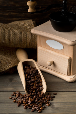 Coffee beans in wooden scoop with wooden coffee bean grinder on dark wooden table background