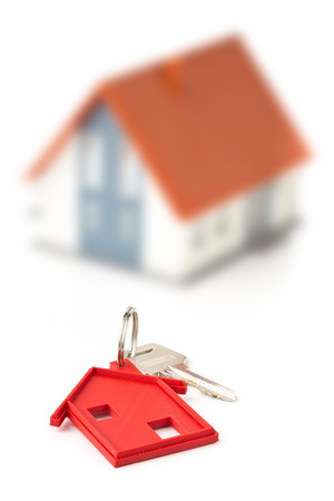 House door key with red house key chain pendant and model house over white background Stock Photo