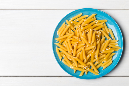 Heap of dried, raw, uncooked penne pasta on blue plate on white table background