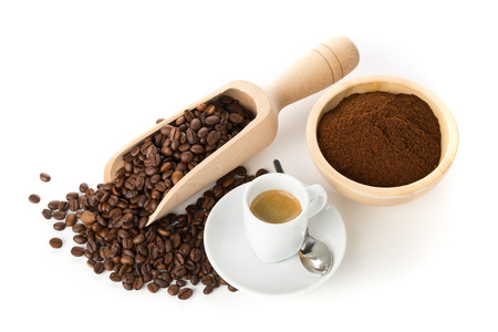 Ground coffee, coffee beans in wooden scoop and cup of espresso on white background