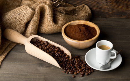 Coffee beans, ground coffee powder and cup of espresso on dark wooden table background