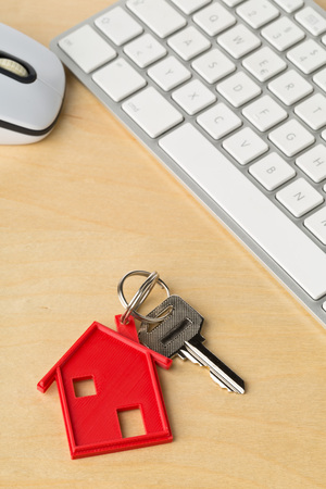House door key with red house key chain pendant and computer keyboard on wooden desk - online house rental or purchasing concept