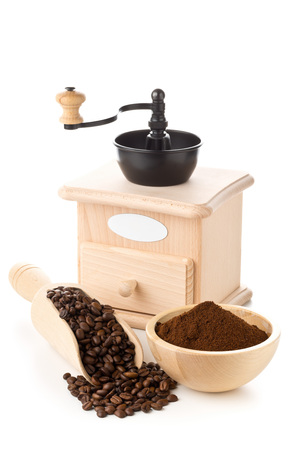 Coffee beans in wooden scoop and ground coffee in wooden bowl with coffee bean grinder over white background