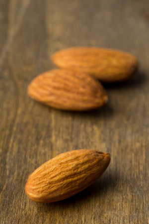 Macro of shelled almond kernels with selective focus on wood background Standard-Bild