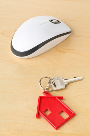 House door key with red house key chain pendant and computer mouse on wooden desk - online house rental or purchasing concept