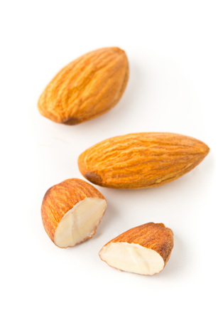 Macro of full and halfed shelled almond kernels with selective focus over white background