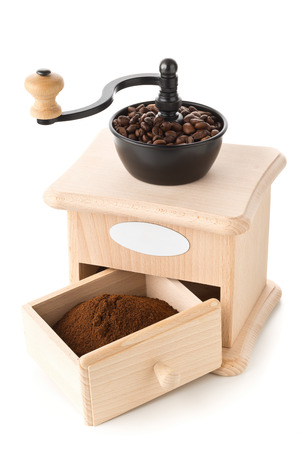 Coffee grinder with ground coffee and coffee beans on white background Standard-Bild