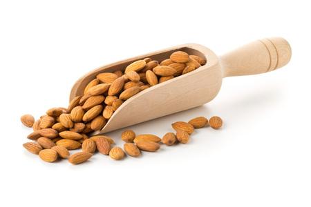 Heap of shelled almond kernels in wooden scoop over white background Standard-Bild