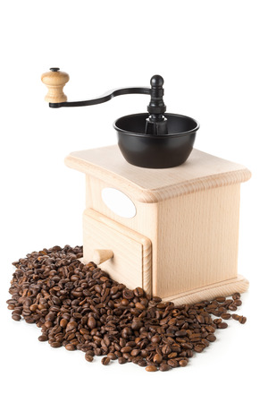 Coffee beans with wooden coffee bean grinder over white background