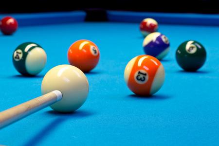Billiard pool eightball taking the shot on billiard table with blue cloth, selective focus on white ball Standard-Bild