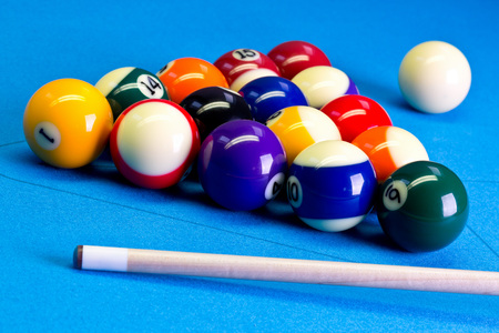 Billiard pool game eight ball with eightball balls set up with cue on billiard table with blue cloth