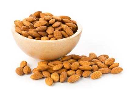 Heap of shelled almond kernels in wooden bowl over white background Standard-Bild