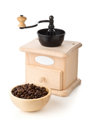 Coffee beans in wooden bowl with wooden coffee bean grinder over white background Standard-Bild