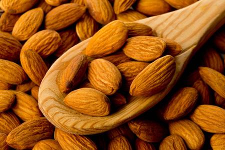 Heap of shelled almond kernels in wooden spoon on almond background Standard-Bild
