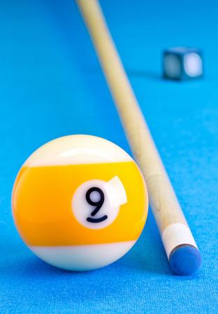 Billiardpool-Spiel neun Ball mit Kreide und Stichwort auf Billardtisch mit blauem Tuch