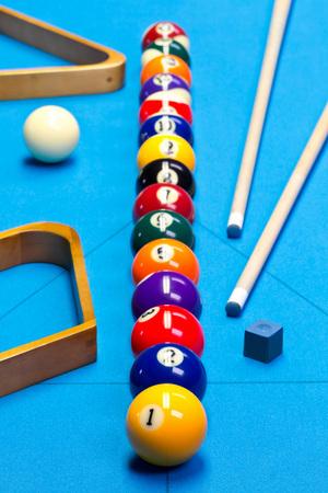 Billiardpool-Spielkugeln aufgereiht auf Billardtisch mit blauem Stoff mit Stichwörtern, Regalen und Kreide