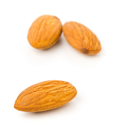 Macro of shelled almond kernels with selective focus over white background