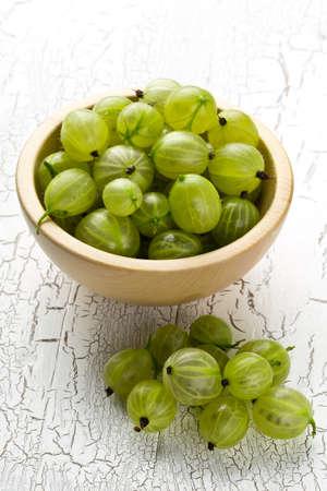 Heap of ripe, fresh harvested green gooseberry fruit in wooden bowl on white table background