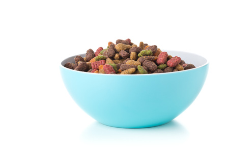 Heap of dry pet food in blue plastic bowl over white background Standard-Bild