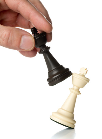 Manager knocking over one chess king figure with another king chess figure - leadership, takeover, promotion or strategy concept over white background