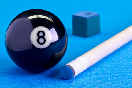 Billiard pool game eight ball with chalk and cue on billiard table with blue cloth