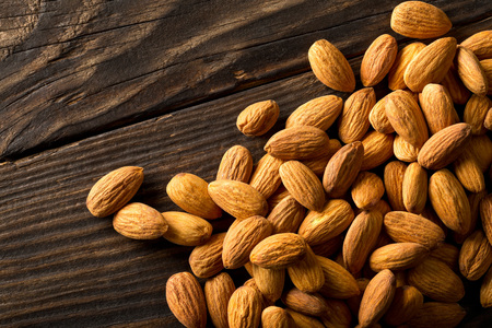 Heap of shelled almond kernels on dark wooden table background