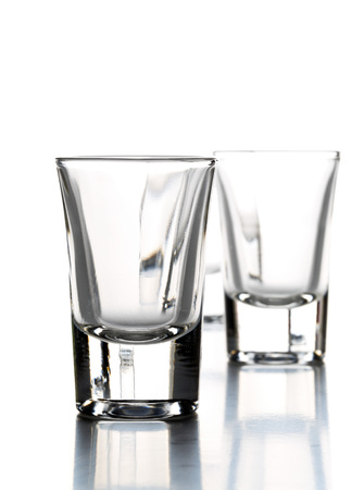 Row of empty shot glasses  over white background