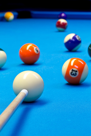 Billiard pool eightball taking the shot on billiard table with blue cloth, selective focus on white ball Stock Photo