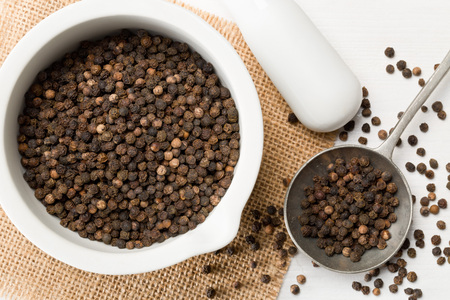 Raw, natural, unprocessed black pepper peppercorns in mortar and metal spoon on white wooden table Archivio Fotografico