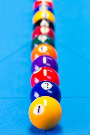 Billiard pool game balls lined up on billiard table with blue cloth, selective focus Stock Photo