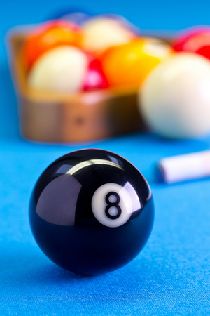 Billiard pool game eight ball with cue and eightball balls set up on billiard table with blue cloth Stock Photo