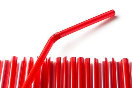 Row of red plastic straws with one straw sticking out over white background Stock Photo